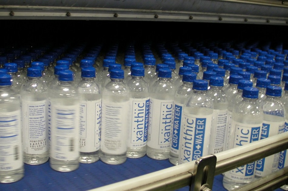 Pictured above: A shot of Xanthic CBD Water bottles exiting the dryer before packaging for shipment. (CNW Group/Xanthic BioPharma)