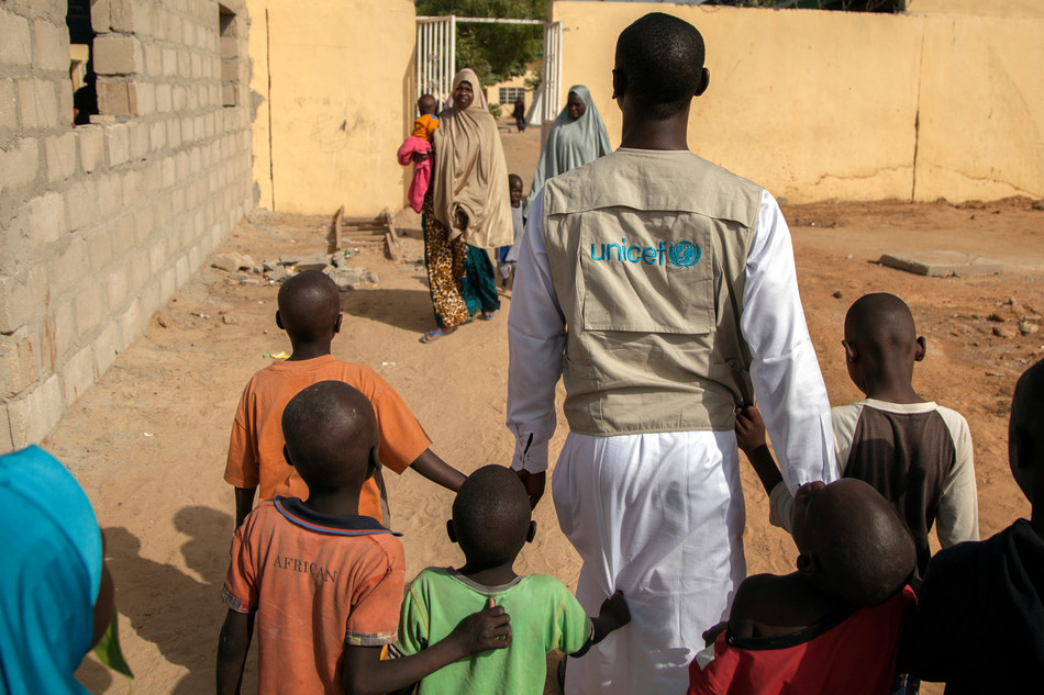 In November 2016, UNICEF Child Protection Officer walks with children at Maiduguri transit centre, Borno State, Nigeria. © UNICEF/UN038572/Naftalin (CNW Group/UNICEF Canada)