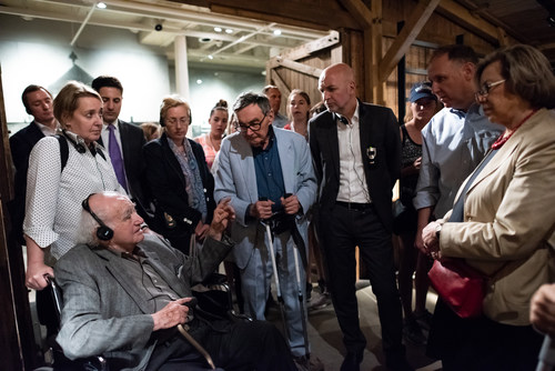 Holocaust Survivor Roman Kent (immediate left) sharing his experience with German State Secretary Dr. Rolf Bosinger (third from right side), in a cattle car like those used to deport Jews, at the United States Holocaust Memorial Museum during negotiations for increased social services for Holocaust survivors. Photo credit: Jason Colston