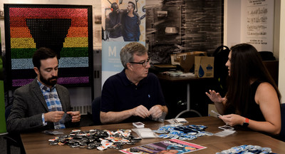 Roberto Ortiz, Executive Director of MAX Ottawa, Mayor Jim Watson, and Sara Leclerc, General Manager at ViiV Healthcare Canada, prepare condom kits for use by MAX at Pride and Spill the Tea events. (CNW Group/MAX Ottawa)