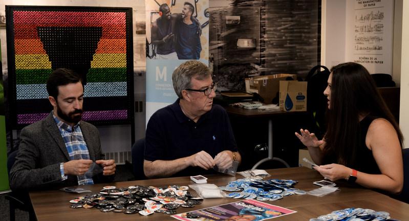 Roberto Ortiz, directeur général de MAX Ottawa, Jim Watson, maire d'Ottawa, et Sara Leclerc, directrice générale de ViiV Soins de Santé Canada, préparent des trousses de condoms qui seront utilisé par MAX Ottawa lors du festivals fierté dans la capitale et  lors de l'évènement « Spill the Tea ». (Groupe CNW/MAX Ottawa)