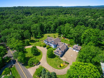 The property sits on nearly 3 manicured acres and is surrounded by dense forestation for added privacy. A semicircular entry and motor court - in addition to 7 garage bays - provide for ample parking. Discover more at ConnecticutLuxuryAuction.com.