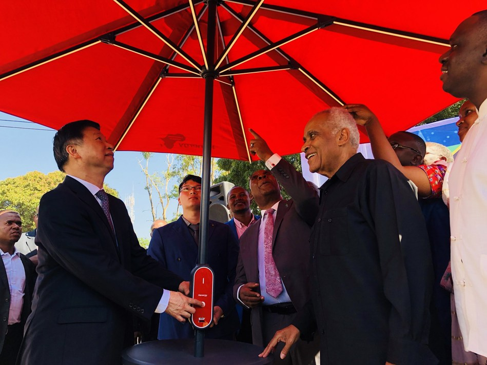 Minister Song Tao and Dr. Salim. Salim lit up the solar umbrella from Hanergy