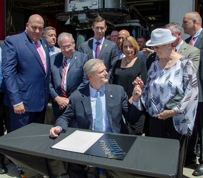 Governor Baker signs bill to designate cancer as work-related injury for state's firefighters. From left, Rich MacKinnon, Professional Fire Fighters of MA, Speaker Robert DeLeo, State Rep.'s Dan Cahill and Lori Ehrlich, and Sharmon Caolarusso, mother of the late Plymouth firefighter Anthony Colarusso, who died from esophageal cancer in 2015 at the age of 39 after losing his health insurance and receiving no paycheck for 93 days.