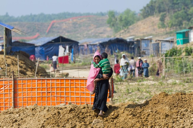 A Rohingya woman and her child walk towards Hope Field Hospital For Women in Madhuchara camp on January 18, 2018, in Cox's Bazar, Bangladesh. (Photo by Rajib Dhar for Direct Relief) (PRNewsfoto/Direct Relief)
