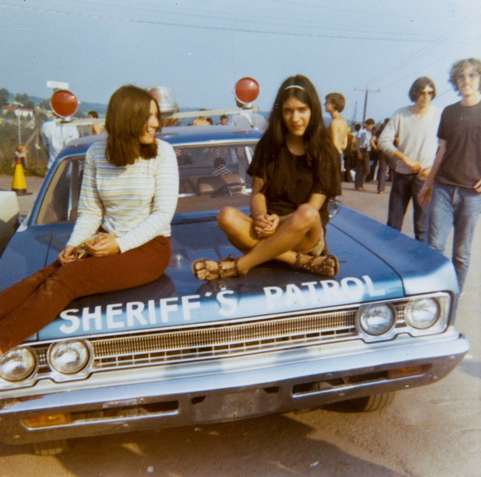 Two young women relax on the hood of a Sheriff's Patrol car at the corner of Hwy. 17B and Hurd Road as people begin to flock into the Woodstock festival. Photo by Elizabeth Alexander. Bethel Woods Collection, gift of Elizabeth Alexander.