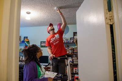 Red Cross volunteers installing smoke alarm and documenting.