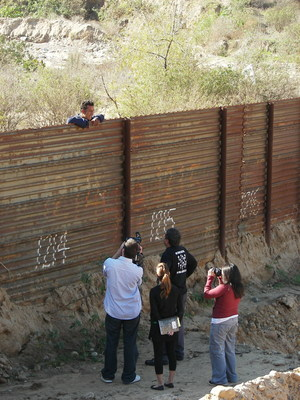 Director Justin Malone and team interview an immigrant across U.S.-Mexico border wall.