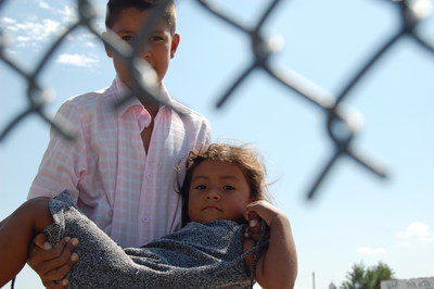 A young brother and sister walk along the border in Juarez, Mexico.