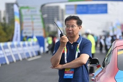 Gaizang Cairang, the head of the Sport Department of Qinghai Provincial government, is supervising the organization of the Tour of Qinghai Lake (Xinhuanet Photo)