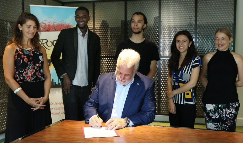 Le Premier ministre Couillard a signé la Déclaration sous le fier regard des jeunes (Groupe CNW/Regroupement des organismes communautaires autonomes jeunesse du Québec)
