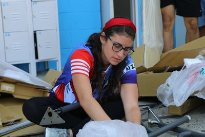 High school senior in Mayagüez helps install a desk for the coming class. Photo Credit: VARIDESK