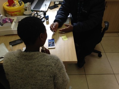 A healthcare worker observing a patient performing HIV self-testing