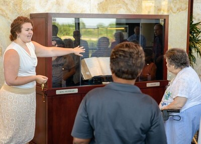 Tour guide showing the displayed bullae to visitors of the Seals of Isaiah and King Hezekiah Discovered exhibit.