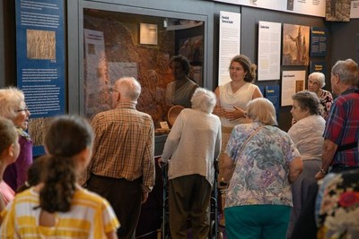 Tour group examining artifacts at the Seals of Isaiah and King Hezekiah Discovered exhibit.