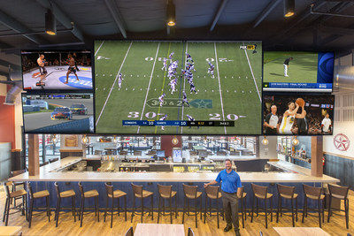 BoomerJacks.com | BoomerJack's Grill & Bar general manager Jason Welch stands beneath the Leyard® TVF Series LED Video Wall from Leyard and Planar. With a 16-foot-long, 9-foot-high screen array in an 8x8 configuration, it's one of the biggest