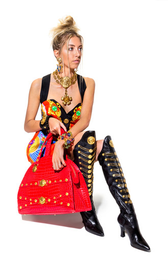 Items to be offered September 21 at Leslie Hindman Auctioneers' The Genius of Gianni Versace auction, modeled by Hannah Warner. Items include blue enamel flag drop earclips; a runway choker; a silk Atelier print mini dress (design from the Spring 1991 runway); a red crocodile embossed Medusa bag; a multicolor floral and Greco link bracelet; and black leather chain boots. The entire collection includes over 350 Gianni Versace designs from the 90s, brought to auction by a single owner.