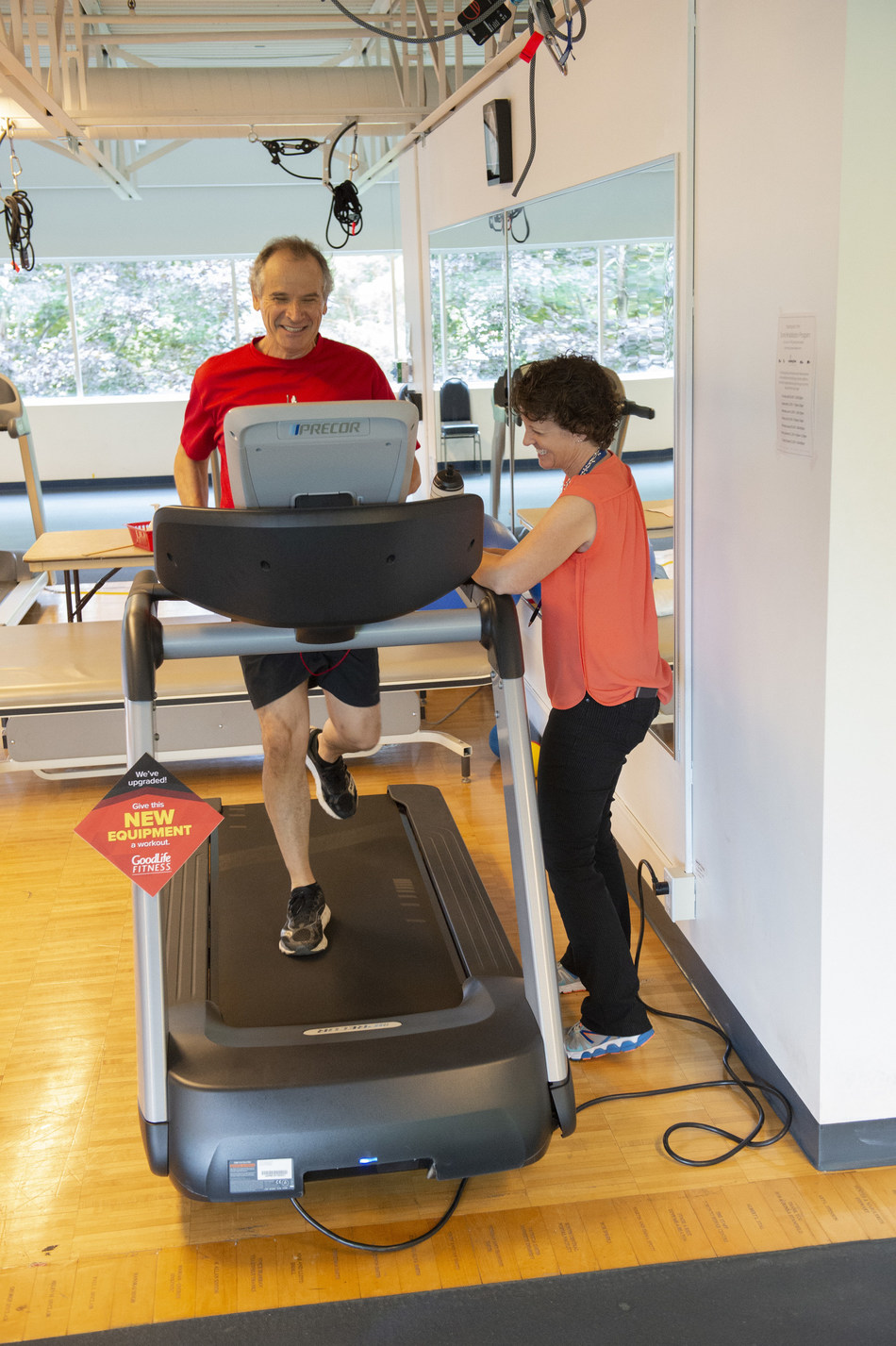 Valerie Skeffington, program manager of PMCC's Cardiovascular Prevention and Rehabilitation Program at UHN, checks in with patient Tony Cesta as he does his cardio workout on a new treadmill at Toronto Rehab's Rumsey Centre. New treadmills, upright and exercise bikes and elliptical machines, worth $330,000, will upgrade the fitness facilities at two UHN cardiac rehabilitation facilities – helping patients connect with physical activity as part of their recovery. (CNW Group/GoodLife Fitness)