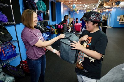 An Ally employee volunteer presents a student with a backpack at The Children Center's Backpack Bazaar on August 21, 2018. Ally volunteers helped distributed more than 800 backpacks full of supplies, uniforms, and hygiene products at The Children's Center's Back to School Bazaar which helps prepare students to kick off the school year with the necessary items.
