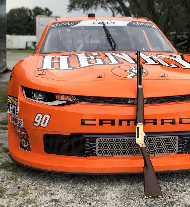 The bright orange car is fully wrapped in a livery for Henry Repeating Arms, a firearms manufacturer well-known for their lever action rifles.