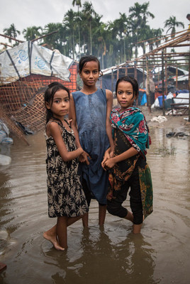 Three girls, all Rohingya refugees, are photographed in the flooded part of the camp where they live in Shamlapur, Cox's Bazar District, Bangladesh (June 2018). © UNICEF/UN0217536/LeMoyne (CNW Group/UNICEF Canada)
