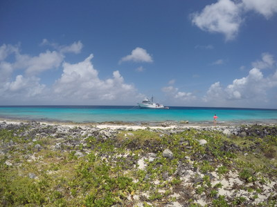 Explorer on the shore of uninhabited Klein Curaçao with R/V Chapman in the distance. Credit: Uncharted Blue