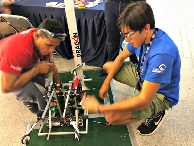 Team UK's Omar Ben-Gacem (right) assisting Team Tonga with a robot repair. (PRNewsfoto/FIRST Tech Challenge)