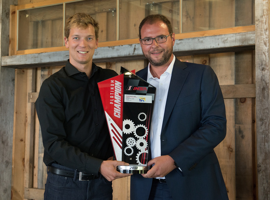 Marc Ouayoun, President and CEO Porsche Cars Canada, Ltd. presents Zacharie Robichon, driver of the No. 98 Mark Motors Racing Porsche and 2018 season champion of the Ultra 94 Porsche GT3 Cup Challenge Canada by Yokohama series, the championship trophy. (CNW Group/Porsche Cars Canada)