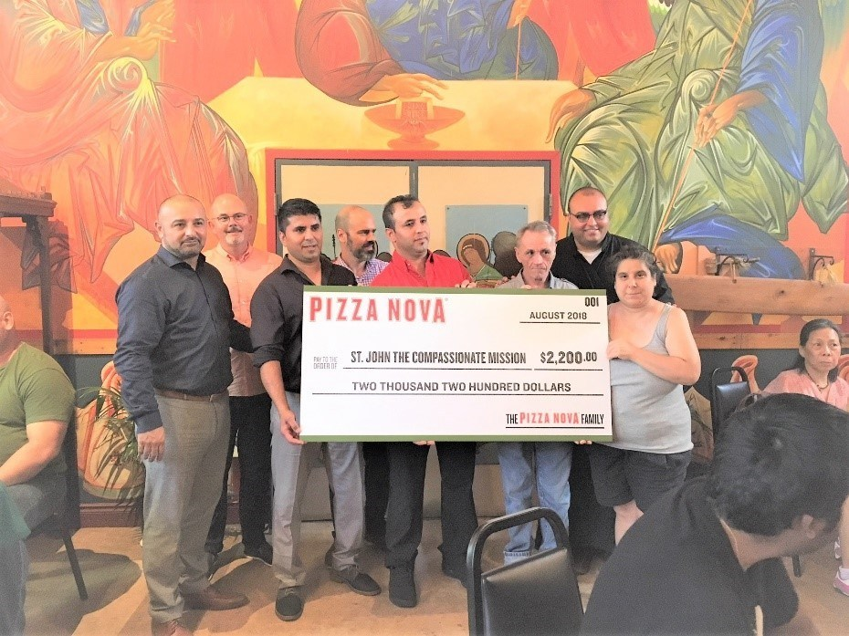 Pizza Nova Director of Franchise Development, Vince Morano (left), District Manager, John Flynn (second from left) and Pizza Nova Director of Marketing, Vince Ambra (middle) along with Franchisees Najib and Mirwais Sharin present the proceeds to representative Deacon Paul of St. John the Compassionate Mission. (CNW Group/Pizza Nova)