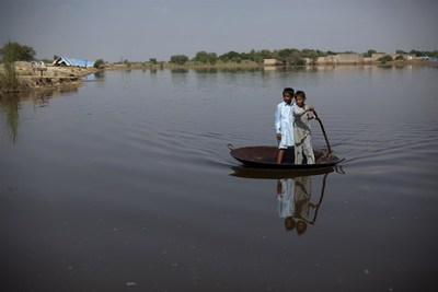 September 2011: Boys use a large steel pot as a raft to cross an expanse of flood water in Nihalbaladi Village, in Khairpur District, Sindh Province, Pakistan. © UNICEF/UNI116709/Zaidi (CNW Group/UNICEF Canada)
