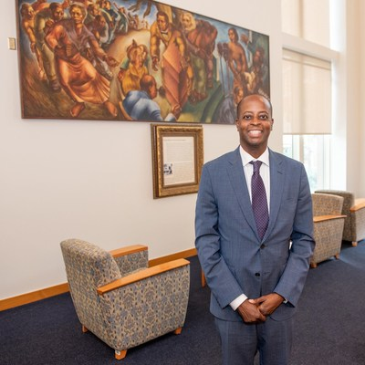 Howard University President Dr. Wayne A. I. Frederick stands in front of Five Great American Negroes, at the Howard University Law Library