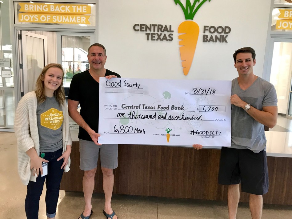 Good Society Co-founders Mark Willis and Brandon Jones present donation check to representative of the Central Texas Food Bank in Austin, TX.