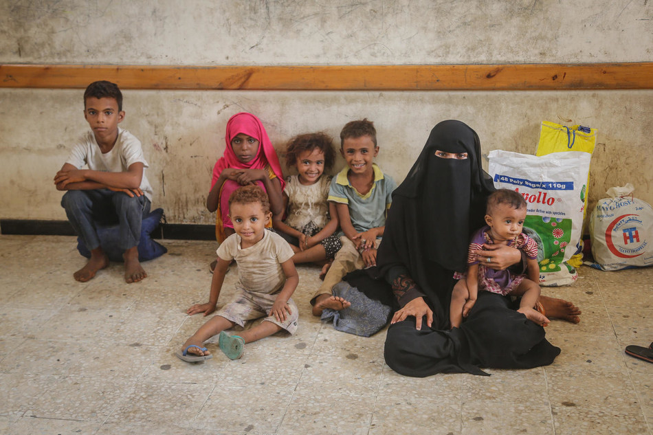 On 30 June 2018 in Yemen, a woman and children wait as UNICEF-supported emergency humanitarian supplies are distributed in Hodeidah. © UNICEF/UN0219932 (CNW Group/UNICEF Canada)