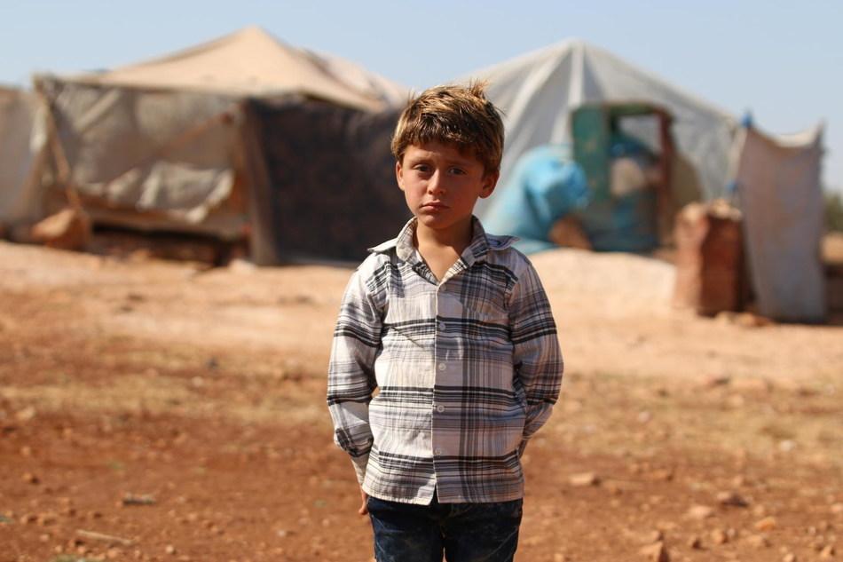 On 21 August 2018 in rural Idlib, Syrian Arab Republic, an internally displaced boy stands near his temporary shelter. © UNICEF/UN0233870/Al Shami (CNW Group/UNICEF Canada)