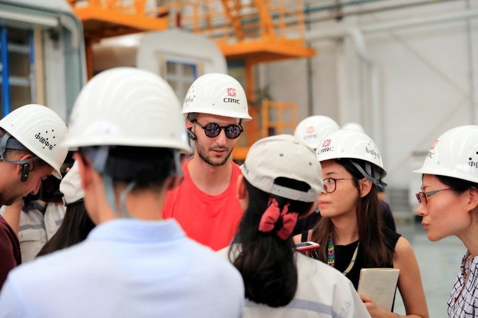 A journalist snaps a photo of the production line of CRRC Qingdao Sifang Company.