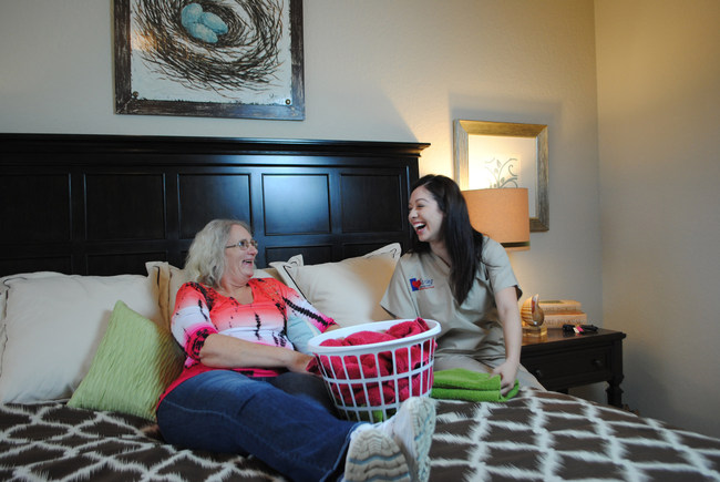 Caring Senior Service caregiver helping a client fold laundry