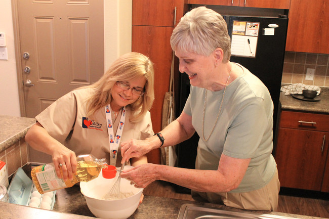Caring Senior Service Caregiver baking a cake with a client