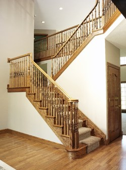The major take-away from the AsktheBuilder.com survey is that for many respondents the ideal staircase would be straight with natural wood grain stained balusters and over-the-post handrails. Photo courtesy of L.J. Smith Stair Systems.