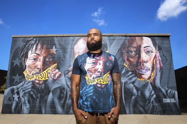 DeAndre Levy in front of Our Issue Mural