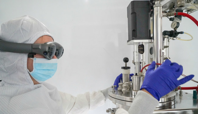 In a cleanroom gown, a lab technician uses Apprentice's conversational UI for a fully immersive AR experience in accessing procedural data and 3-D technique demonstrations on how to prepare a bioreactor.