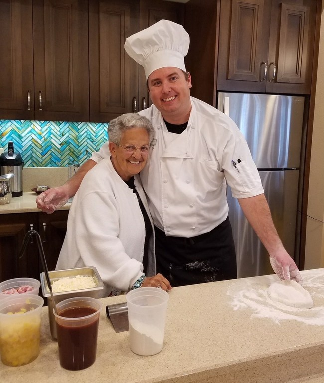 Executive Chef Ryan Gorsuch shares a hug with Mrs. Nancy Cote during an interactive pizza demonstration with residents at Market Street Memory Care Residence in Viera.
