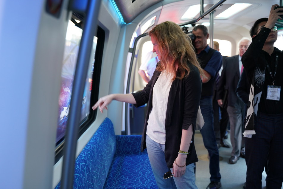 Media and visitors show great interests in CETROVO's magic window, which can transform into a touch-screen and allows passengers to perform tasks like watching videos and even paying tickets on it. (PRNewsfoto/CRRC)