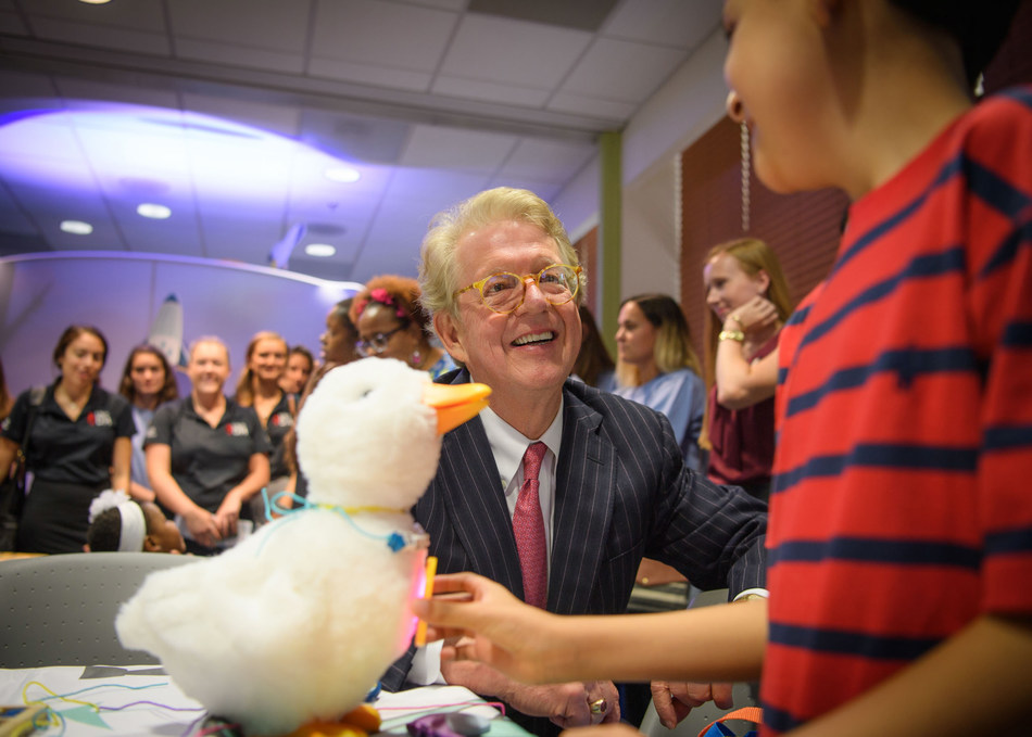 Aflac Chairman and CEO Dan Amos huddles with 8 year old cancer patient Alexander Montes with the My Special Aflac Duck at an event held at Palmetto Health Children's Hospital in Columbia, South Carolina