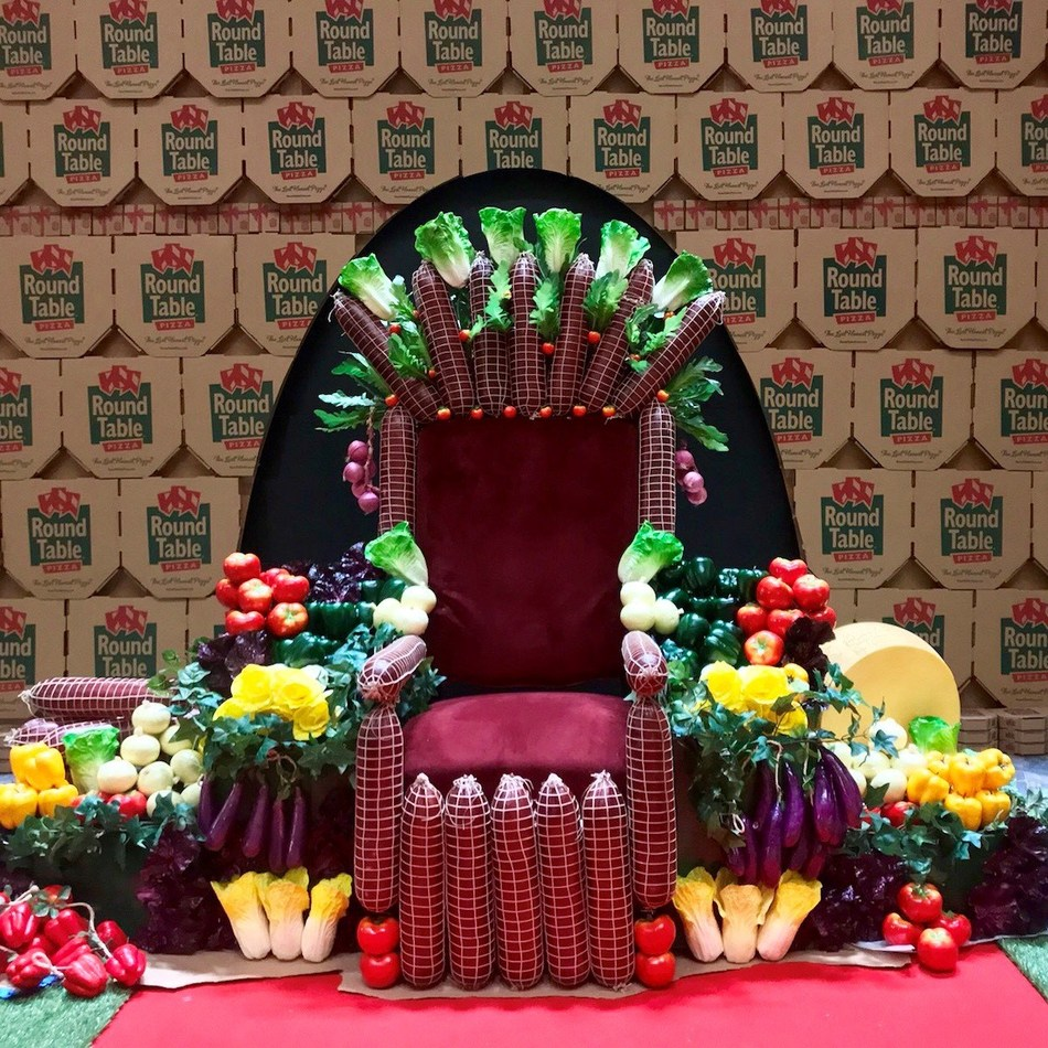 Visitors to The Pizza Experience in L.A. can sit on a throne made of toppings while enjoying a slice of Round Table Pizza(r)
