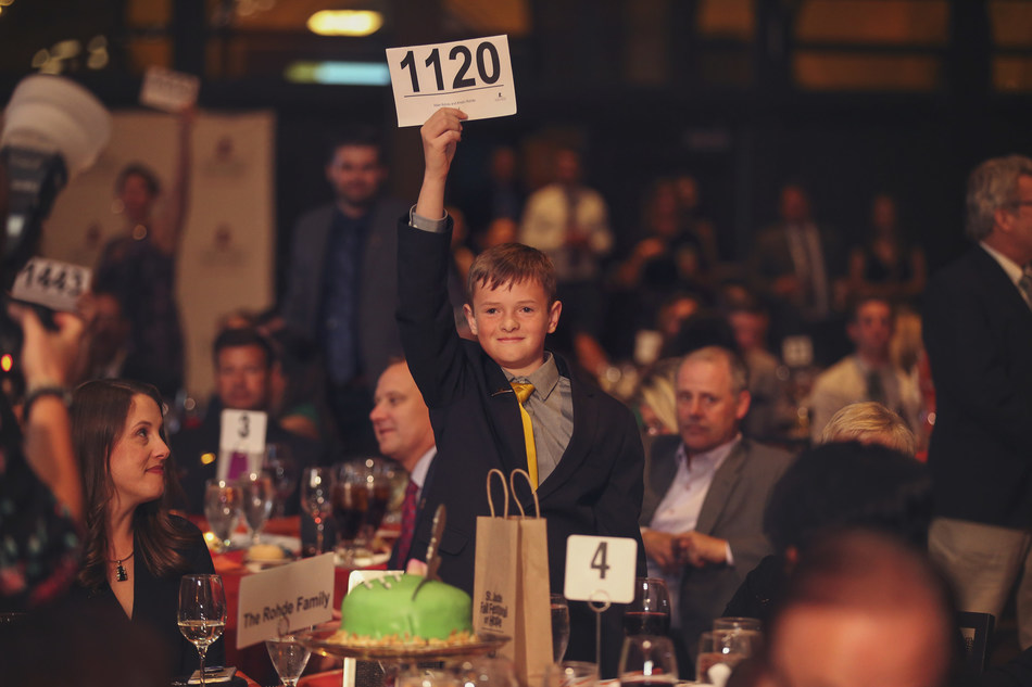 Pictured is Aiden, brother of St. Jude patient Connor who passed away from cancer. When he stood and raised his auction paddle at the St. Jude Fall Festival of Hope, he inspired the entire room to stand and break fundraising records in Connor's memory.
