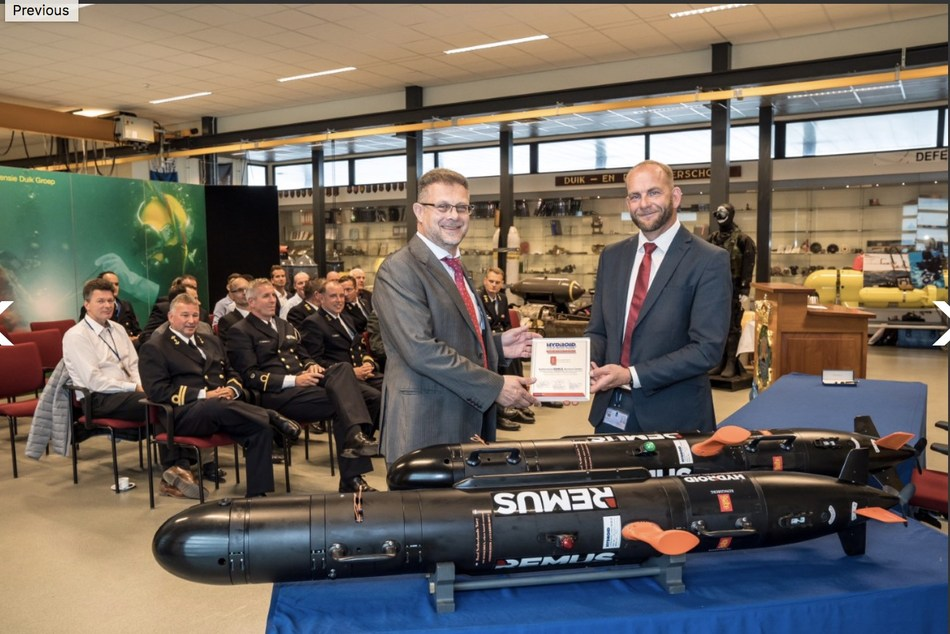 Graham Lester, senior vice president of sales and marketing for Hydroid, presents Mr. Arnold Boomstra, head of Sensors and Weapon Systems, Directorate of Material Support, with a certificate recognizing the Royal Netherlands Navy as an authorized REMUS Service Center.
