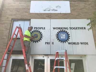 Ken Kueng, senior superintendent at JP Cullen, the construction firm that built the GM plant in 1919 and is now building the Legacy Center, removing the sign from the front entrance of the GM plant that will be displayed at the Legacy Center