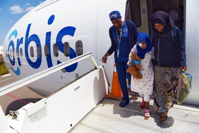 Orbis staff nurse Gloria Rhomes assisted Rahmet, age 9, from the Flying Eye Hospital after her cataract surgery in Addis Ababa, Ethiopia.