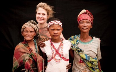 Photographer Dana Gluckstein poses with three generations of San women.