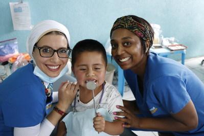 Dr. Reham El-Hennawey, endodontist, and Yara Almedia, dental assistant, with a local young boy providing dental care.